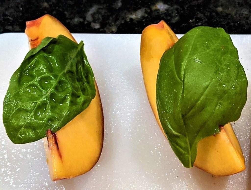 peach slices with basil leaf on top