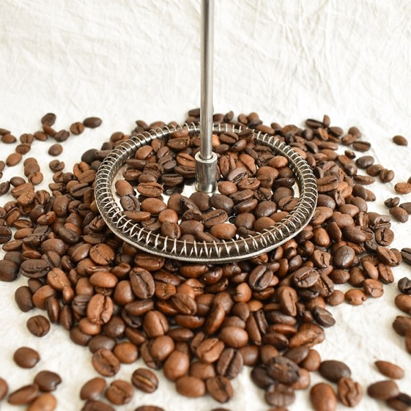 Brazilian coffee bean with a french press screen on top