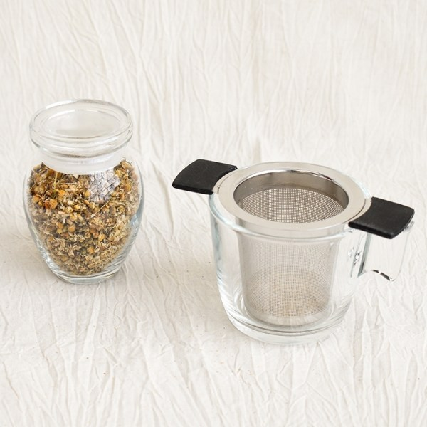 Chamomile flower in a jar and an empty glass with a tea strainer