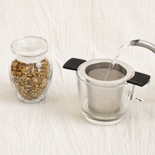 Chamomile flower in a jar, chamomile tea brewing in a glass