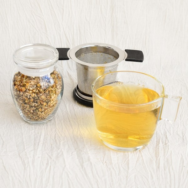 Chamomile flower in a jar, chamomile tea in a glass, used tea strainer in the background
