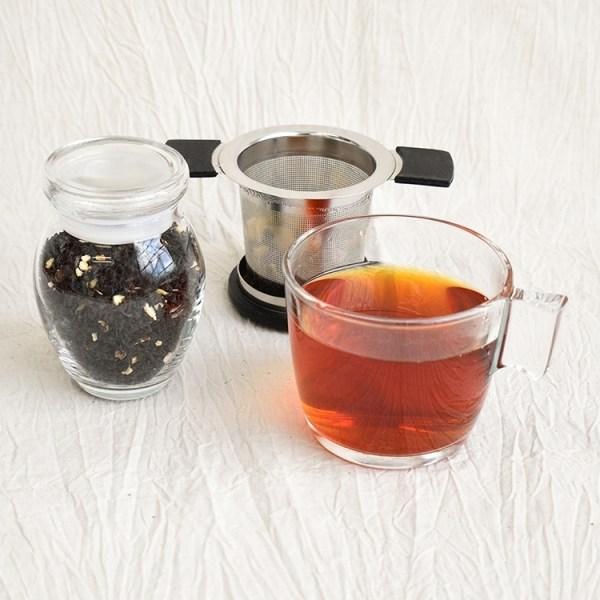 earl grey tea leaves in a jar, earl grey tea in a glass, used tea strainer in the background
