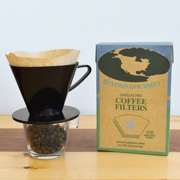 Black coffee cone dripper on top of a glass and a box of unbleached coffee filter