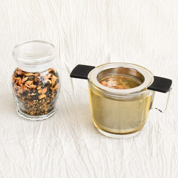 Jasmine green tea leaves in a jar, jasmine green tea brewing in a glass