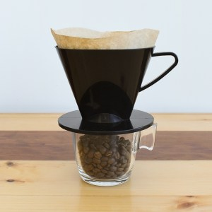 Black coffee cone dripper on top of a glass filled with coffee beans