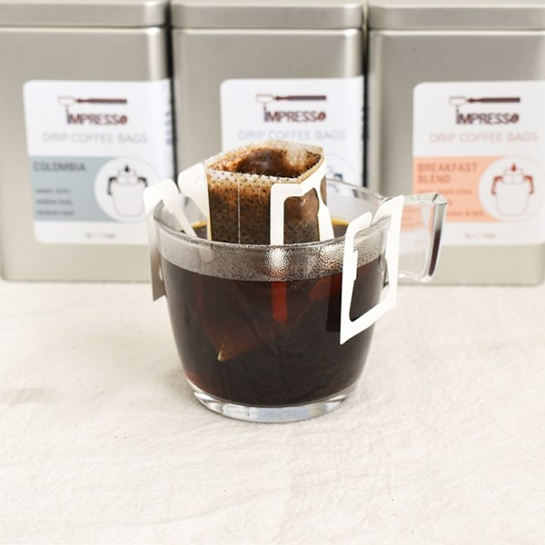 Drip coffee bag brewing in a glass