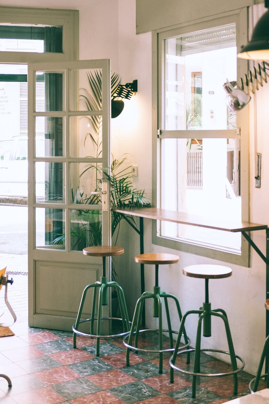 interior of stylish cafe with wooden counter and stools placed near window