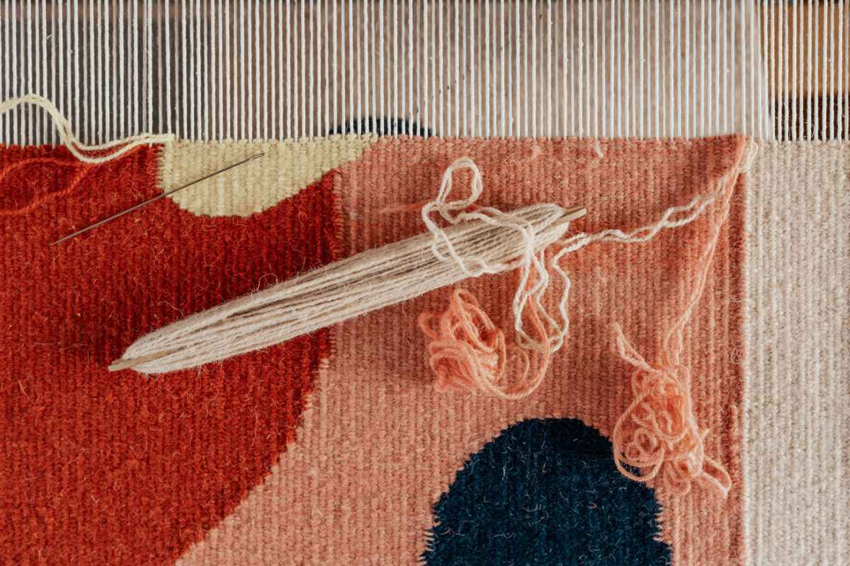 unfinished handmade tapestry with shuttle on hand loom