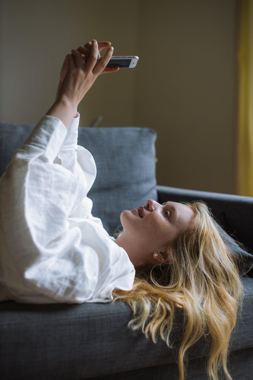 woman in white dress shirt lying on a sofa
