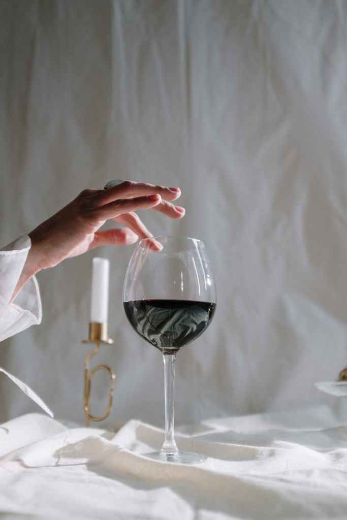person holding clear wine glass