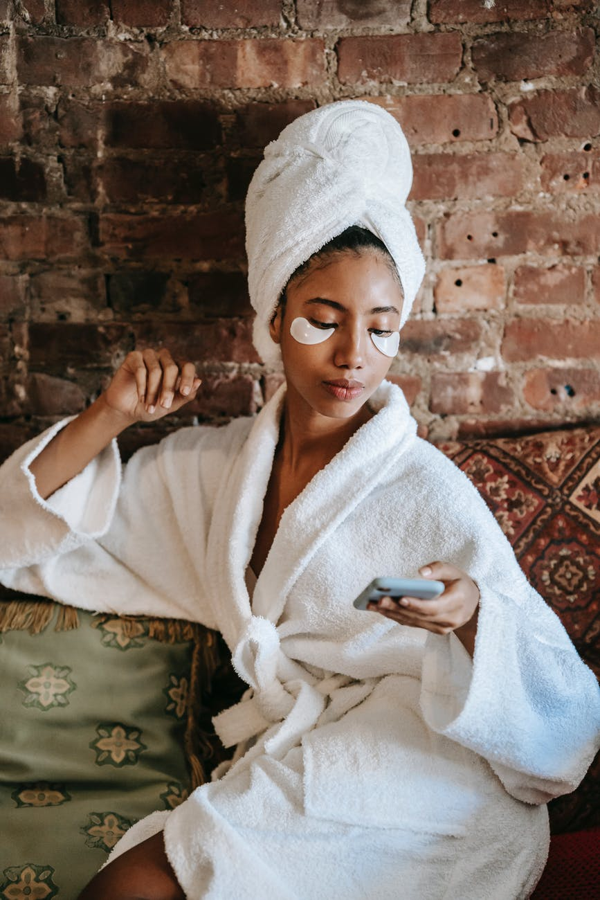feminine ethnic woman chatting on smartphone in beauty salon