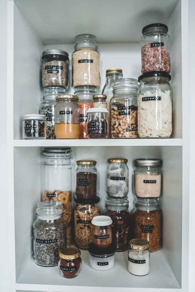 clear glass jars on white wooden shelf