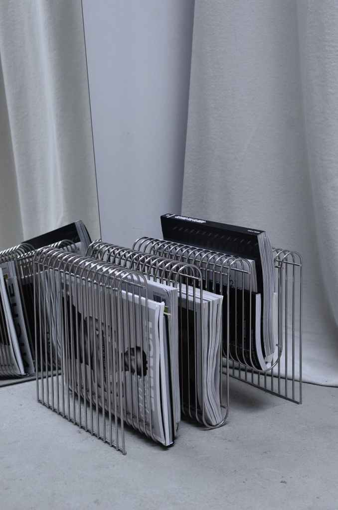 magazines in stand placed on floor in room corner