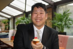 image of Jon Nguyen, smiling and holding a cupcake