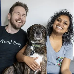 Stephen and Vithiya are posed with Ernest (a large brown dog), smiling.