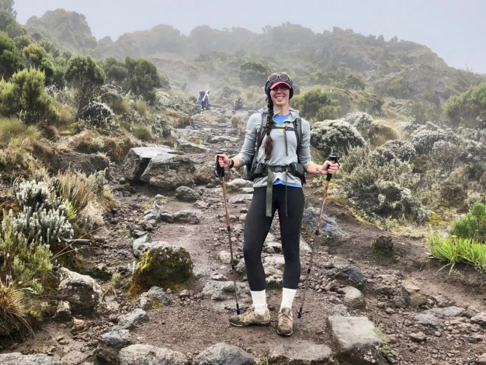 A hiker on the steeper path that is edged with stubbier vegetation along the Machame path towards Kilimanjaro.
