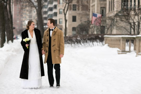 Newlyweds strolling the snow covered lawn