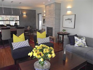 Open living area remodel with new stone-clad fireplace and wall sconce lights on sides accent wall behind dining table with two large mirrors horizontally installed and modern pendant light fittings yellow scatter cushions on deep blue slipper chairs and grey corner sofa with throw cushions