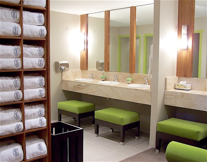 Gym bathroom with ottomans at vanity area