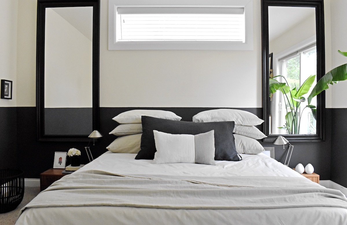 Master bedroom with large mirrors and horizontal strip painted in a strong color