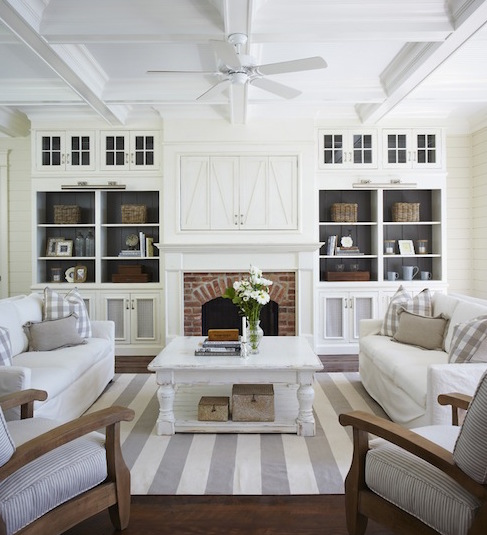 tv above the fireplace and behind doors in a cottage style