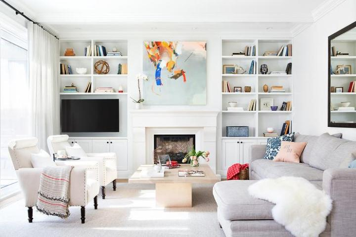 v next to fireplace with shelf unit in a casual room