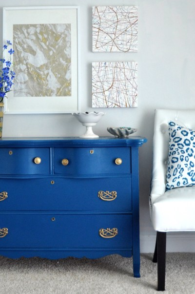 Blue painted dresser with throw cushion and fresh flowers in same colour with muted neutral tones