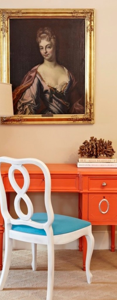 Secretaire painted in bright orange colour brightens the raditional setting