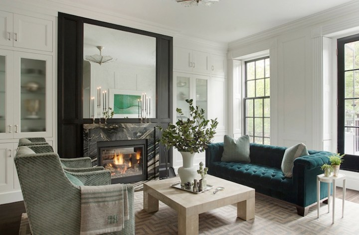 Classical chesterfield sofa in peacock blue with delicate side table and contemporary coffee table in living room with fireplace