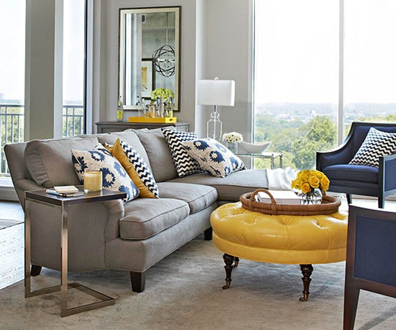English sofa in contemporary living room with blue chairs and yellow ottoman