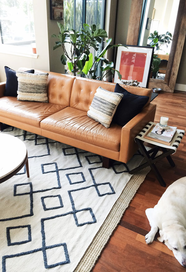 Tan leather sofa with tufted back in Erin Hiemstra's mid-century living room with black and washed stone