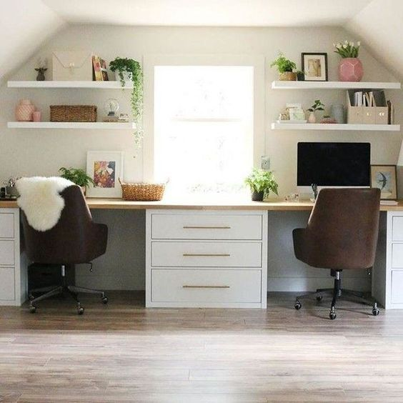 Home office in attic with leather chairs, wall shelving and large pedestals