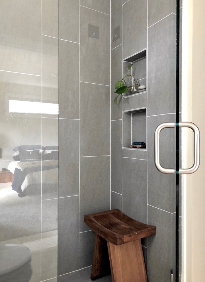Bathroom walk-in shower with vertical tile running bond tile double niche and frameless glass