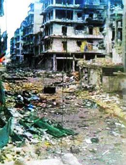 Ein ehemaliger Nachbar von Khalil, der gerade zu Besuch war, zeigt auf seinem Smartphone dieses Foto. In dem fünfstöckigen Haus im Hintergrund befand sich der kleine Supermarkt von Khalil und seiner Familie.