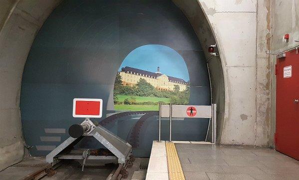Im U-Bahnhof Bensbergendet die Linie 1 der KVB an einer Betonmauer. Das Bild zeigt das Kardinal-Schulte-Haus