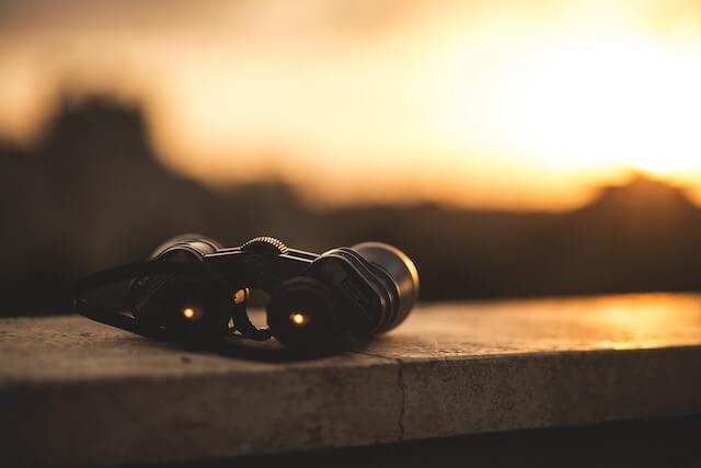 Binoculars sitting on ledge during sunset