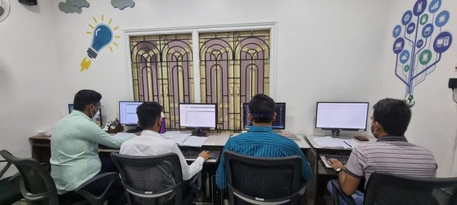 Four men working at a desk at Instance IT Solutions