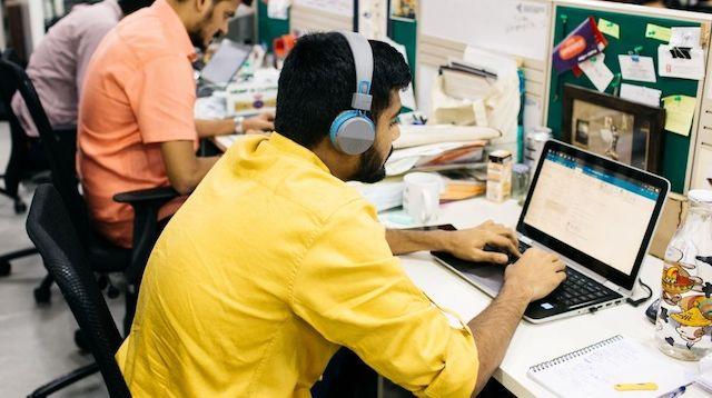 Three men working at laptops