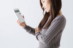 looop電気にしたのに安くなっていないので電卓を見つめる女性