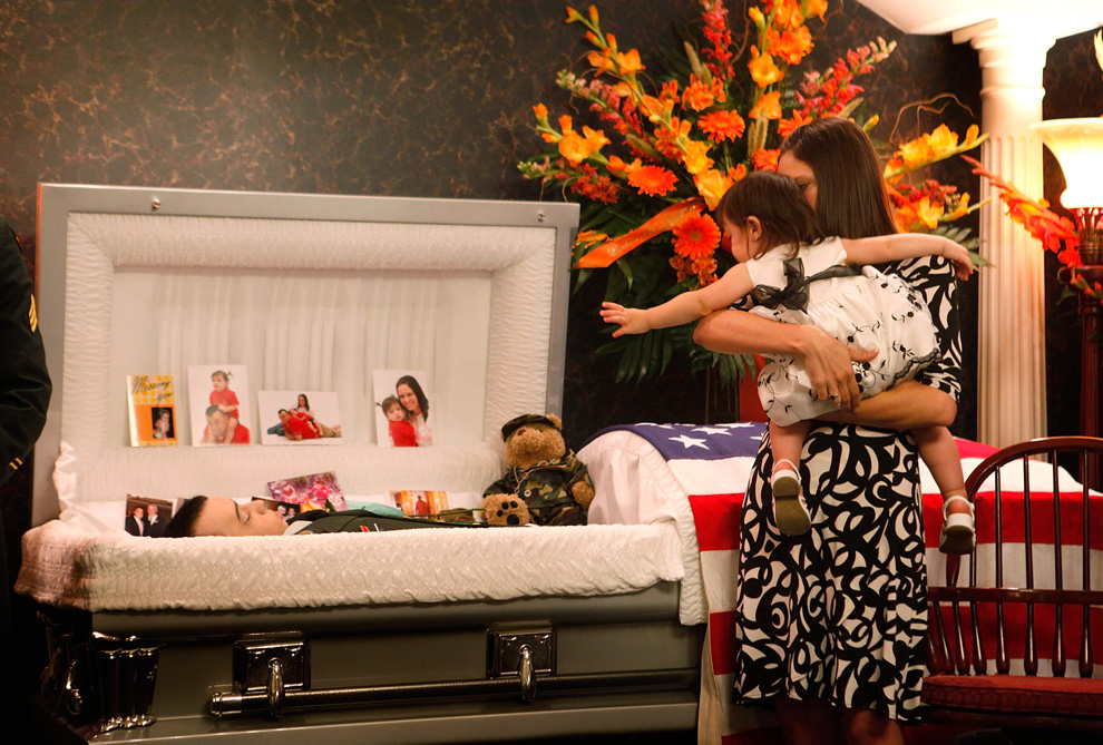 Sixteen-month-old Aubrey Melton reaches for her father, SSG Josh Melton, as she views his body with her mother Larissa before his funeral service on June 27, 2009 in Germantown, Illinois. SSG Melton, who was serving in Afghanistan with the Illinois National Guard, was killed in Kandahar during an IED attack on June 19. (Scott Olson/Getty Images)