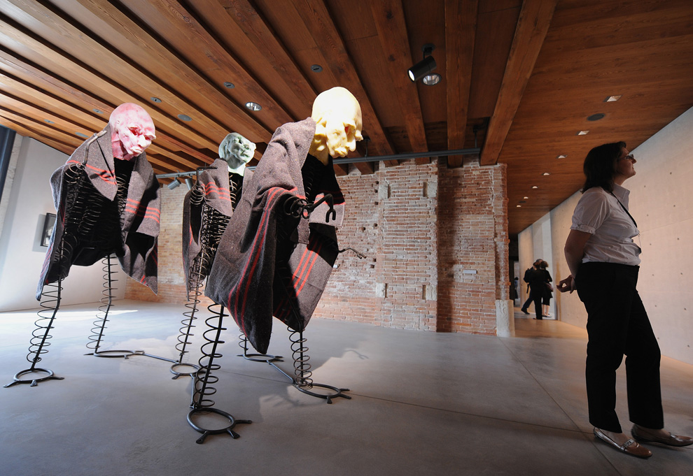 A woman stands near German artist Thomas Schuttes Efficiency Men 2005 on show during the opening of the Punta della Dogana in Venice on June 3, 2009.
