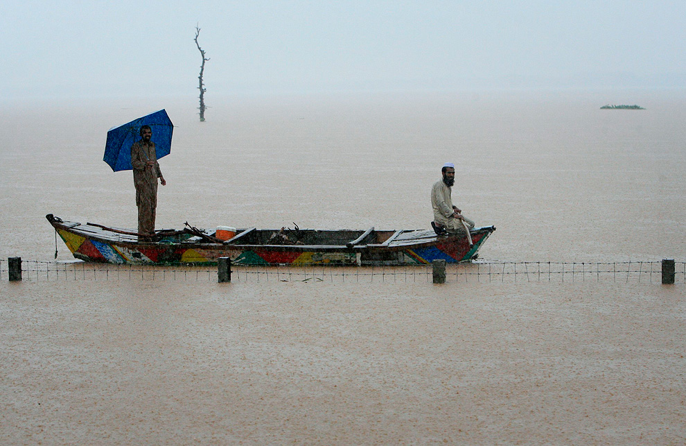 Men take refuge on a boat during heavy rain in Pakistan's Nowshera District on July 29, 2010. (REUTERS/K. Parvez)