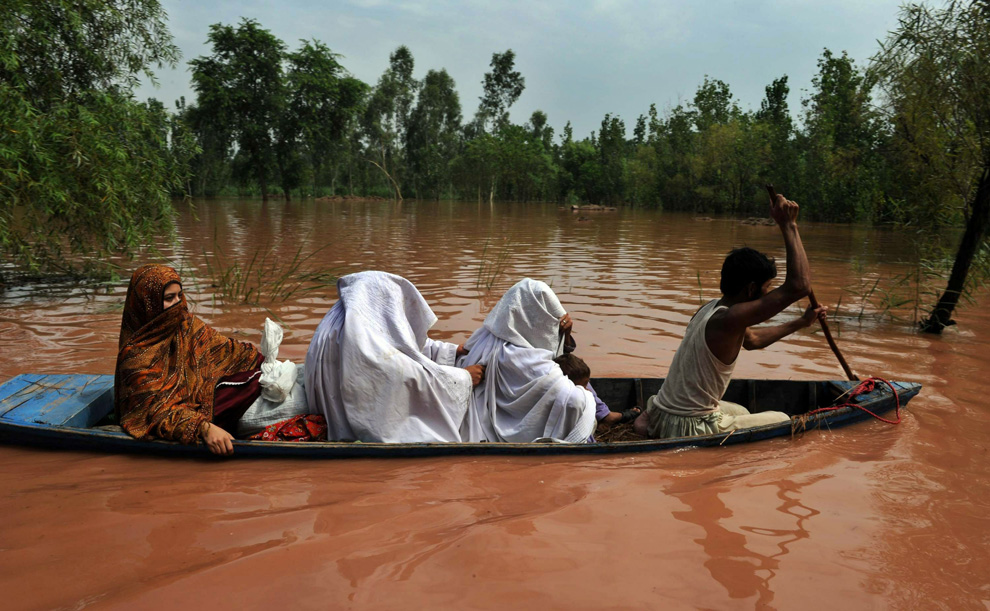 A Pakistani volunteer uses a small boat to evacuate locals in a flood-hit area of Nowshera on July 30, 2010. (A. MAJEED/AFP/Getty Images)