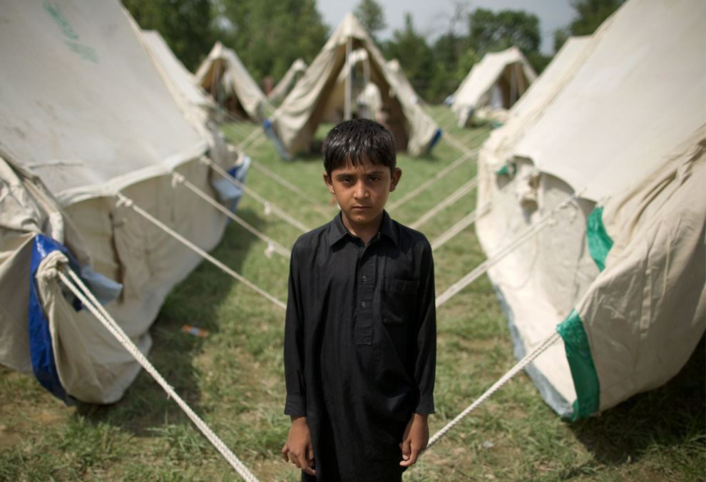 A Pakistani boy named Jeeshan stands outside his tent in a camp set up by the Pakistani army inside a college on the outskirts of Nowshera on August 2, 2010. (BEHROUZ MEHRI/AFP/Getty Images)