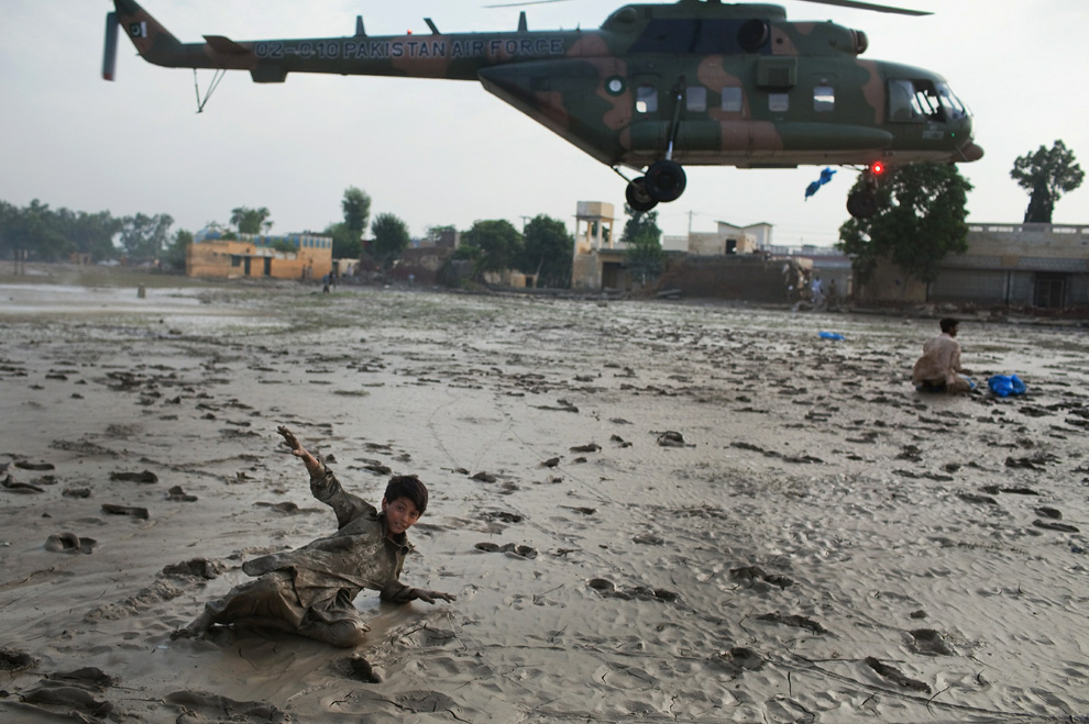 A boy is flung back by the force of a Pakistan Air Force helicopter rotors as it drops water supplies to residents on August 2, 2010 in Nowshera, Pakistan. (Daniel Berehulak/Getty Images)