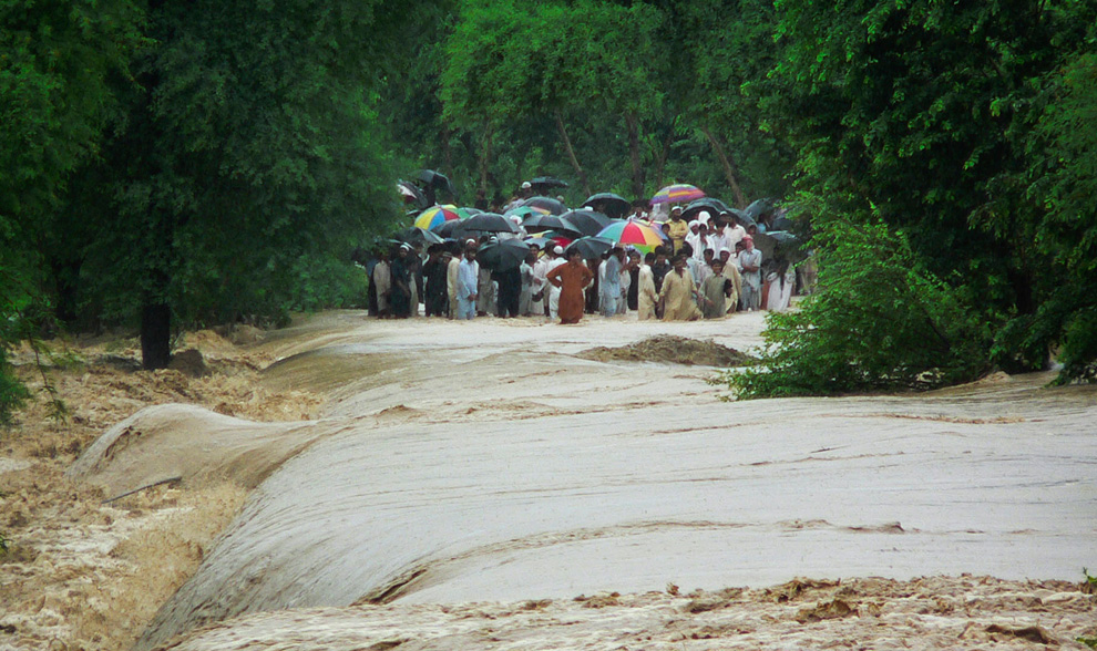 People wait to cross a flooded road in Bannu, northwestern Pakistan on Tuesday, Aug. 3, 2010. (AP Photo/Ijaz Mohammad)