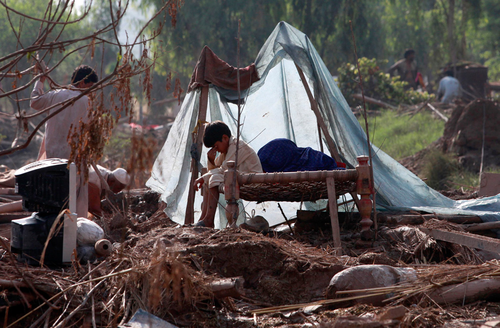A boy sits on a bed as his family members salvage belongings from their destroyed house in Pabbi, Pakistan on August 5, 2010. (REUTERS/Faisal Mahmood)