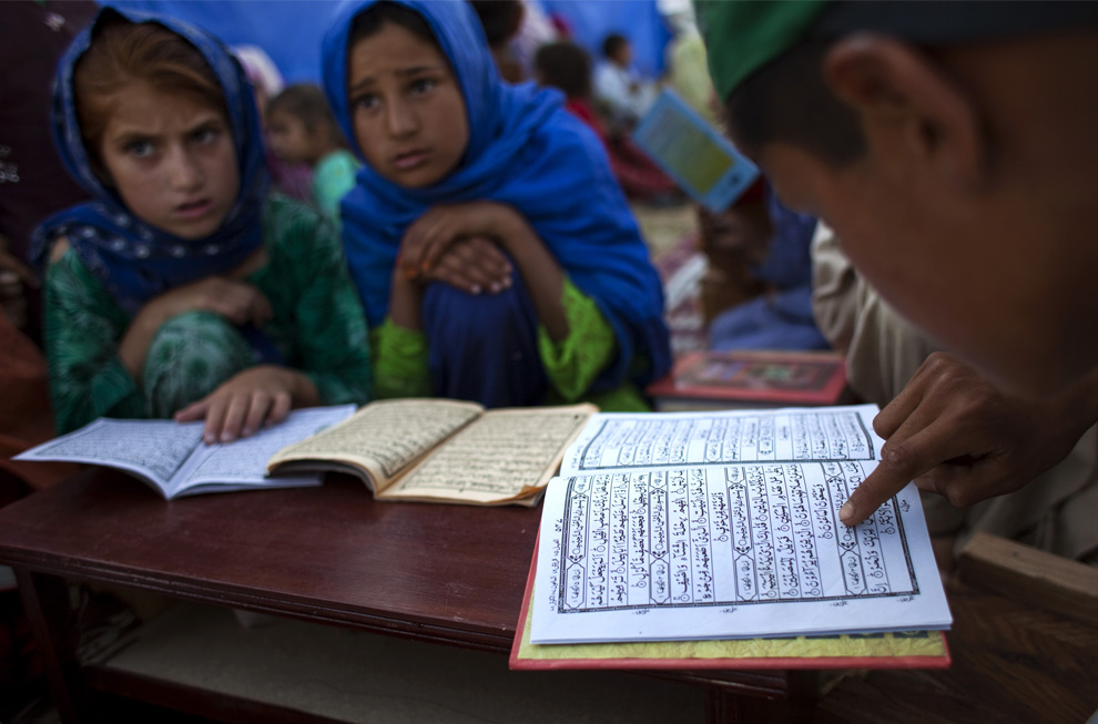 Displaced children memorize the Quran at a madrassa in a camp [AP Image]