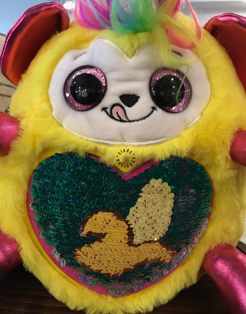 A soft and cuddly yellow creature equipped with a tuft of rainbow hair, a unicorn horn, shiny pink ears and limbs, and a sequined heart in the middle of it's tummy displaying a banana.