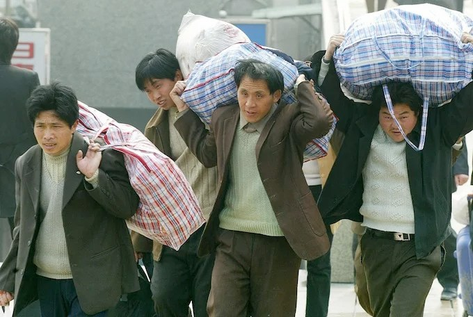 Migrant workers carry goods in Shanghai,